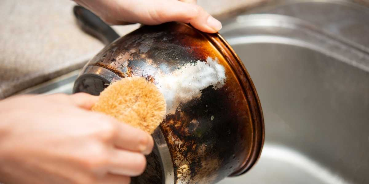 Woman washing scorched pot with soft sponge.