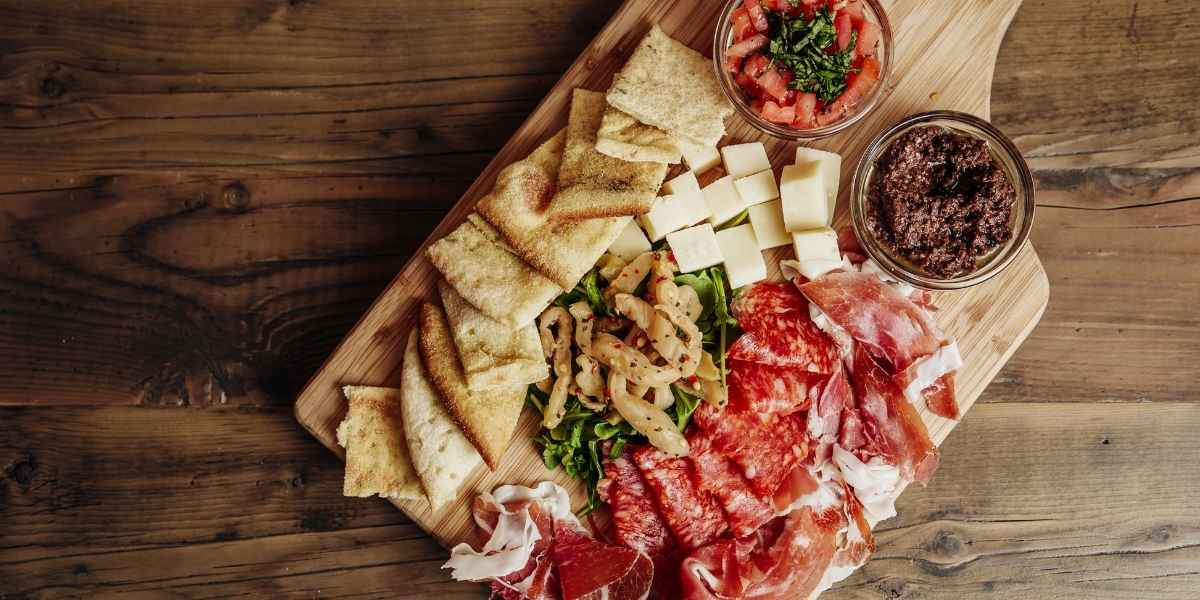 charcuterie spread with meat on wooden cutting board