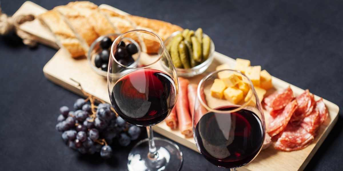 Wine and charcuterie spread with dried meats, cheese, grapes, and more