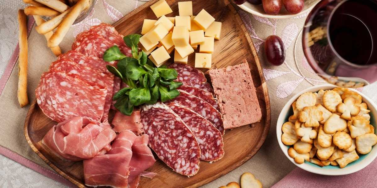 example of date night cheeseboard crackers, cheeses, meat on charcuterie board