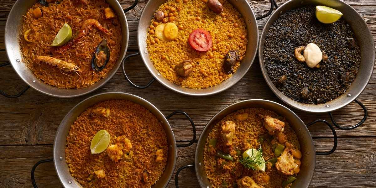 multiple types of paella and one noodle based dish in various paella pans