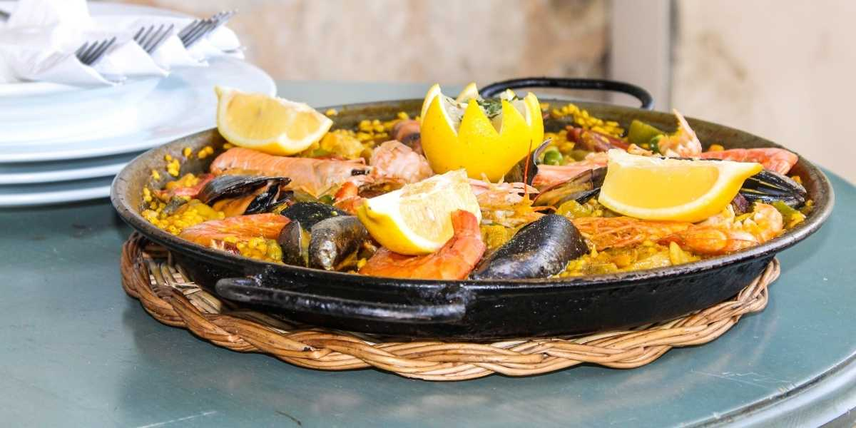 paealla serving in small paella dish ready to eat seafood paella enameled paella pan