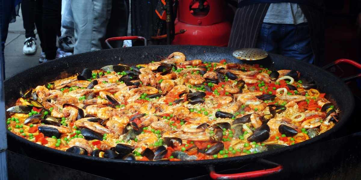 seafood paella in paella pan laid out on wooden surface