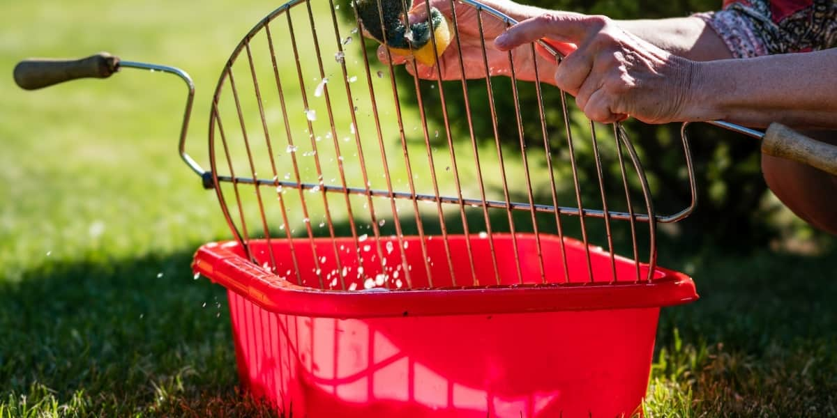 Man soaking grill grate in water and wiping off leftover grime.