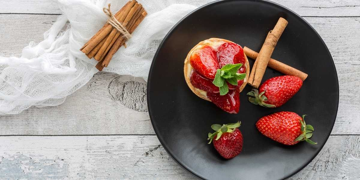 Strawberries and cinnamon sticks on plate and laid out with baked strawberry pie treat
