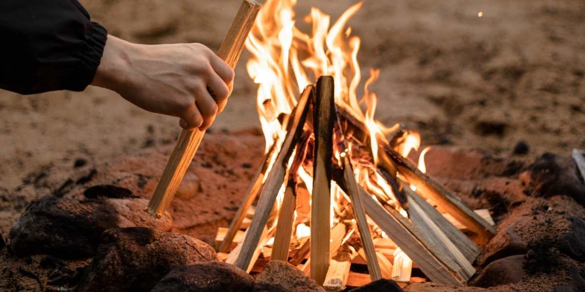 wood fire campfire cooking fire for paella paella pan teepee formation beach machika