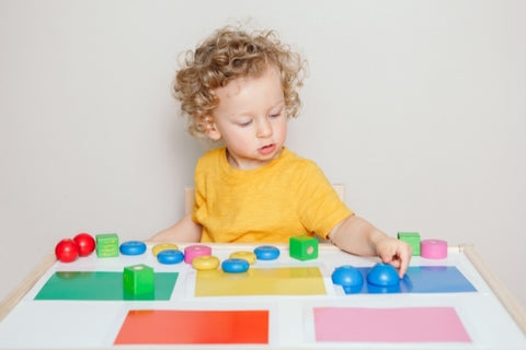 Child sorting toys by colour