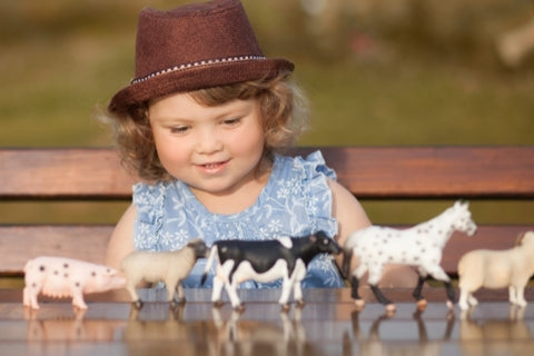 Child playing with domestic animal toys
