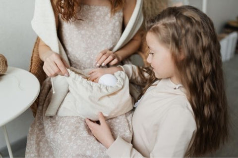 A girl playing with mother pulling out toys out of the magic bag