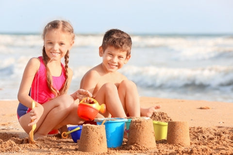 Kids making sand towers on the beach