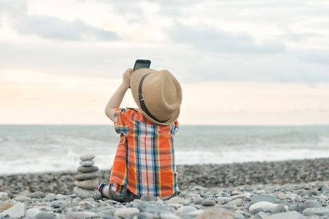 Kid taking pictures on the beach