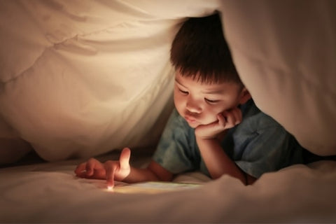 A child under duvet scrolling the tablet screen