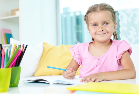 Little girl smiling and writing