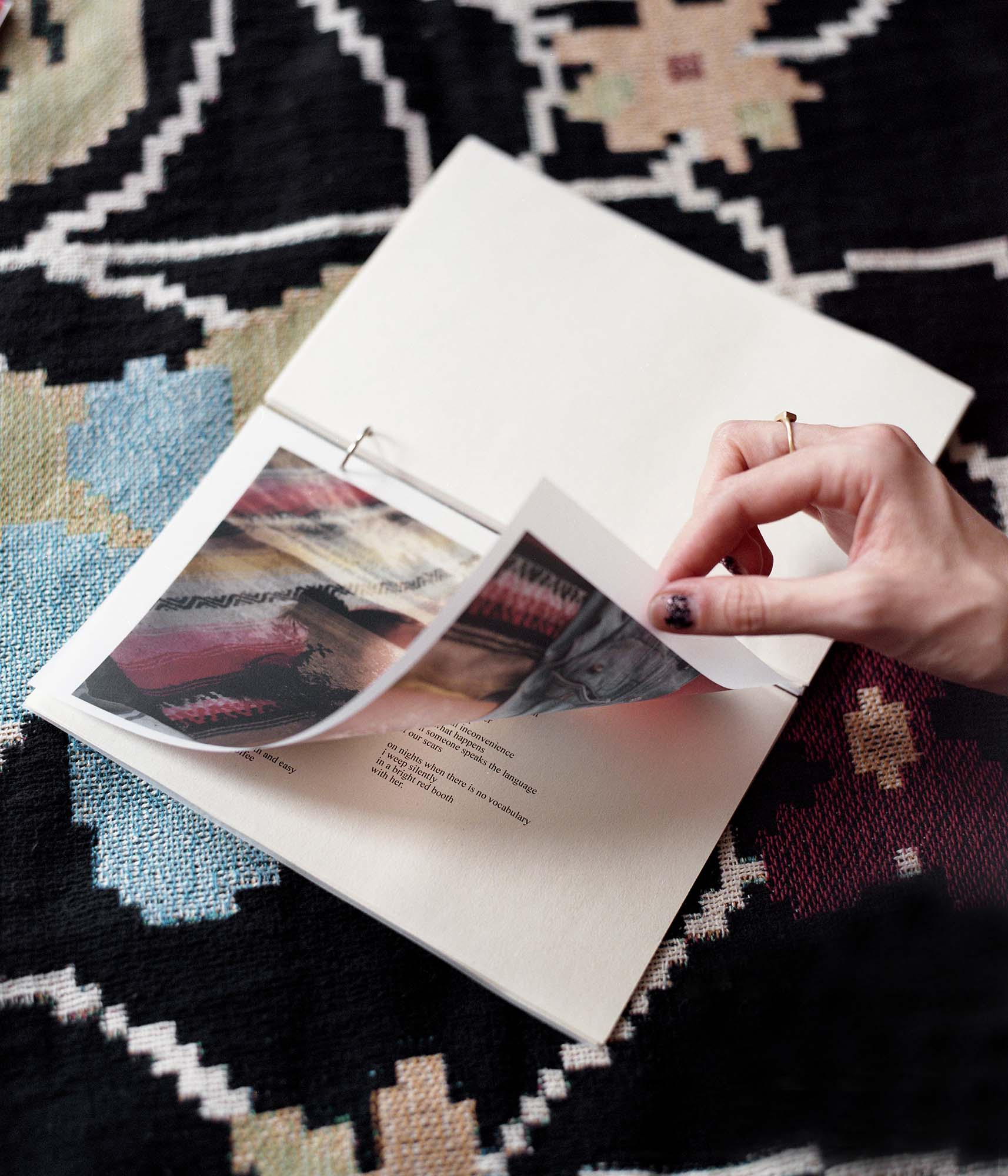 film photo of tess flipping a page in the book, so you can see the transparent vellum paper