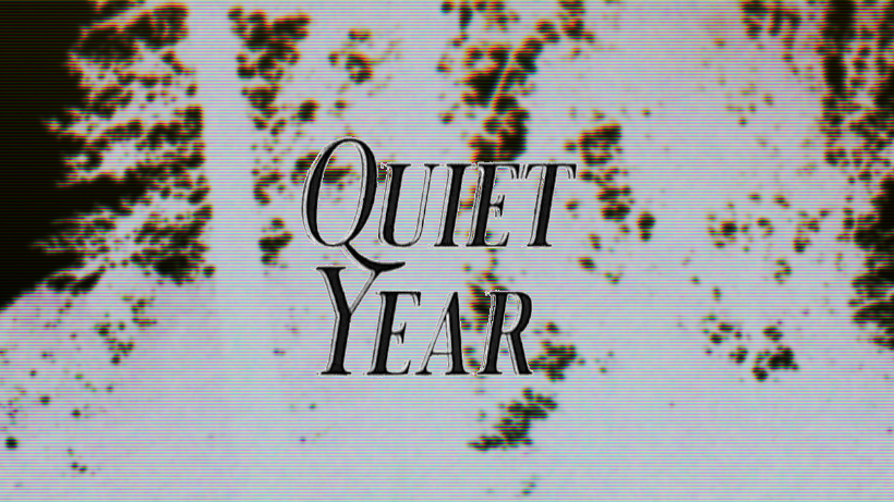 Black Quiet Year logo on inverted photo of trees