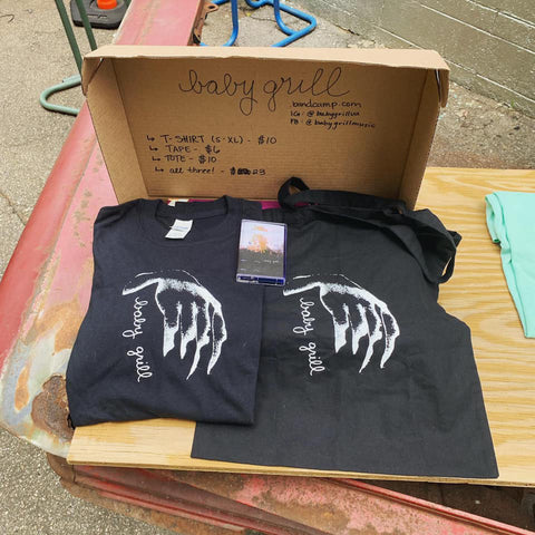 "Image of two Baby Grill Handy tees. A white outstretched hand is dangling while ""Baby Grill"" is oriented vertically under its wrist in cursive font."