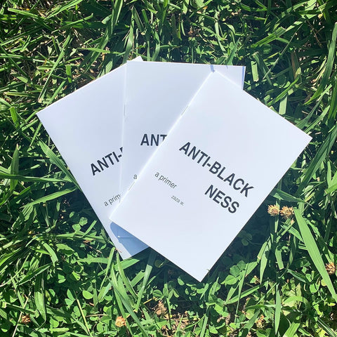 Three Anti-Blackness: A Primer zines are splayed out in a field of grass and four-leaf clovers.
