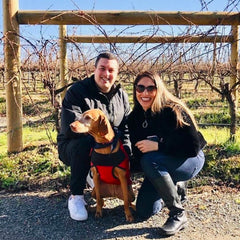 A man (Diego) and woman (Mazzy) posing in front of vineyard with their Hungarian visla dog connie