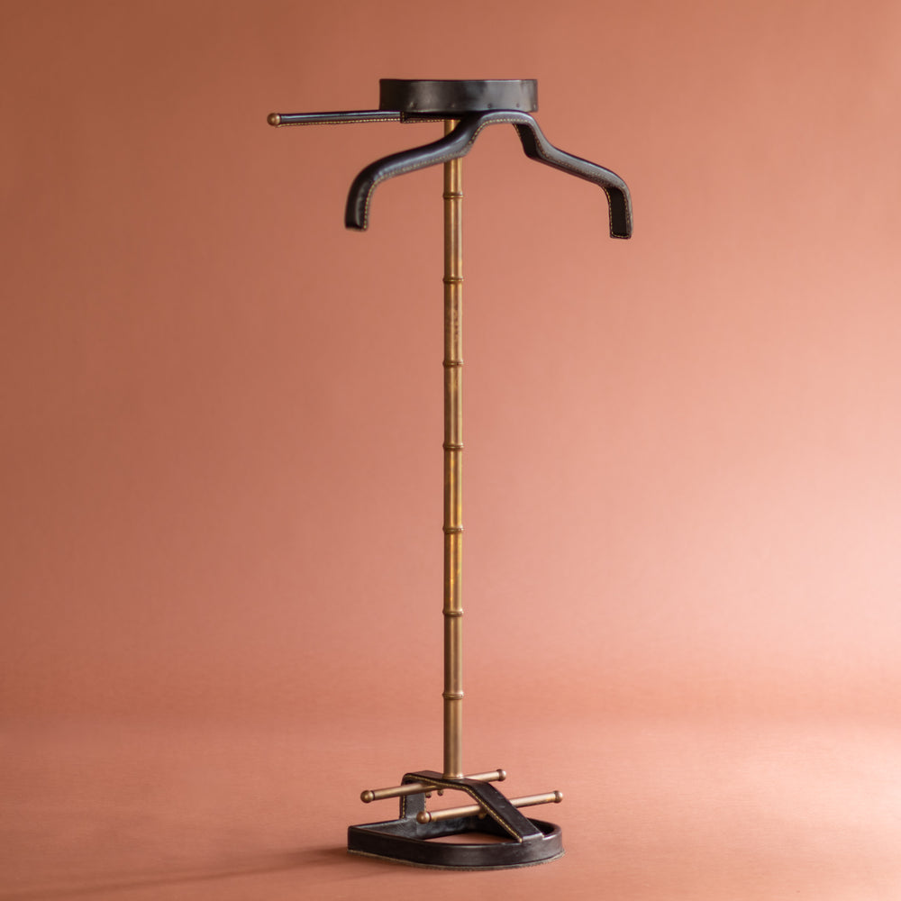 An angled front view of a 1950's Valet de nuit; model 'Luxe' by Jacques Adnet, France. The vertical central tubular brass stand is made to look like bamboo. The base is leather in the shape of a horseshoe and it has a leather hanger at the top at an angle.