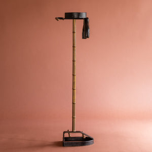 A side view of a 1950's Valet de nuit; model 'Luxe' by Jacques Adnet, France. The vertical central tubular brass stand is made to look like bamboo. The base is leather in the shape of a horseshoe and it has a leather hanger at the top at an angle.