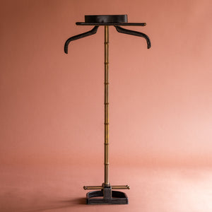 A front view of a 1950's Valet de nuit; model 'Luxe' by Jacques Adnet, France. The vertical central tubular brass stand is made to look like bamboo. The base is leather in the shape of a horseshoe and it has a leather hanger at the top at an angle.