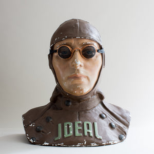 Front view of painted brown and beige plaster cast bust of air pilot wearing vintage motoring or aviation goggles with fine mesh and fabric strap by Kraus & Co, facing front. Word ideal across chest. White background.