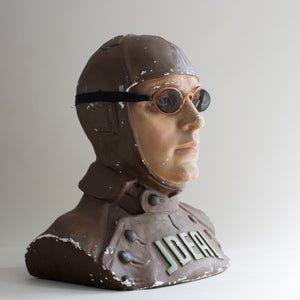Side view of painted brown and beige plaster cast bust of air pilot wearing vintage motoring or aviation goggles with fine mesh and fabric strap by Kraus & Co, facing right. White background.