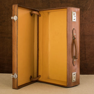 Sitting open on it's side showing the yellow Rexine lining inside of the leather case, on the right side showing the handle and nickel plated brass locks, circa 1925. Brown and cream background.