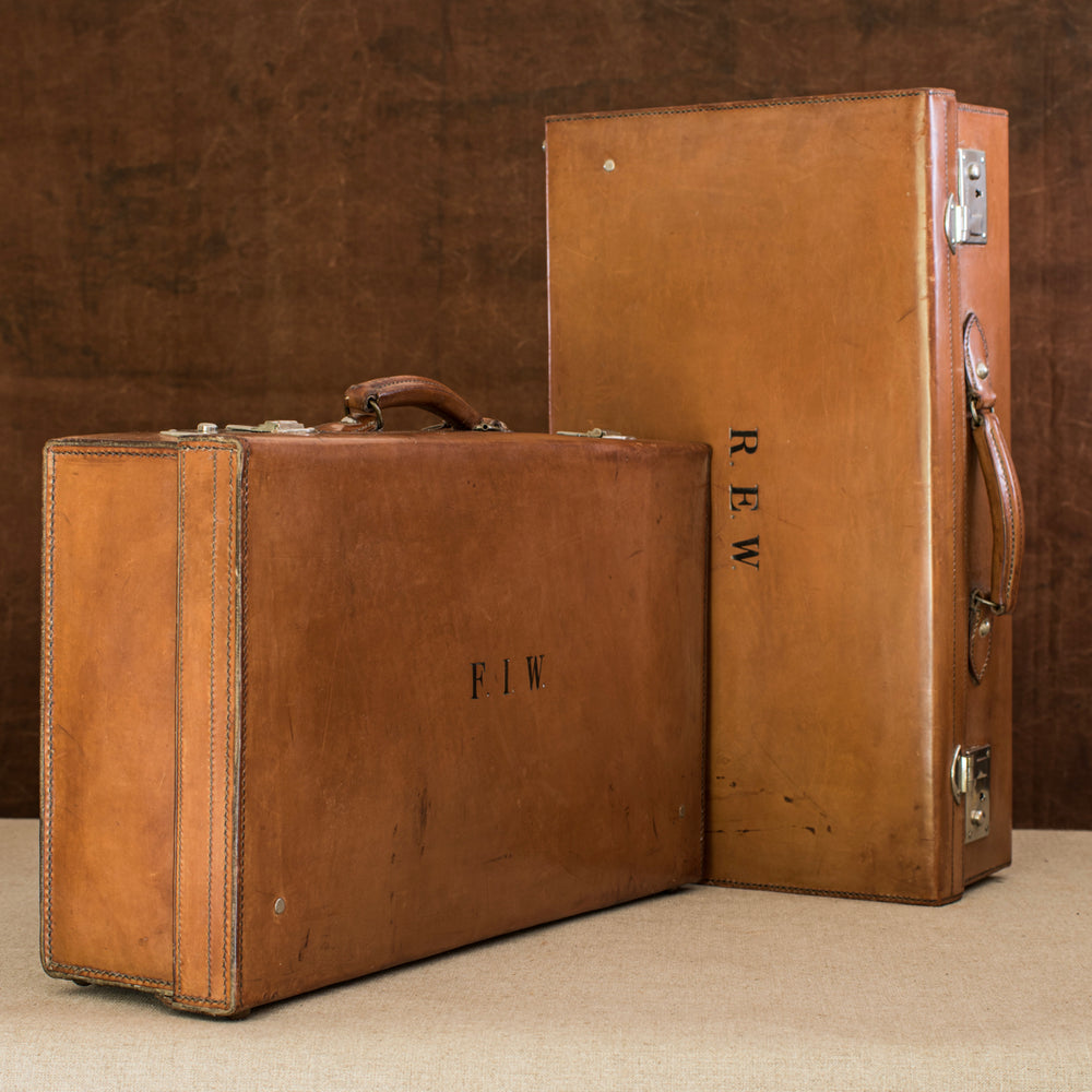 A matching pair of English leather cases, circa 1925. On the left the suitcase is at a diagonal angle with the embossed initials F.I.W. lid facing the right and handle at the top. On the right the suitcase initialed  R.E.W. is on it's side with the handle facing right. Both have nickel plated brass locks. Brown and cream background.