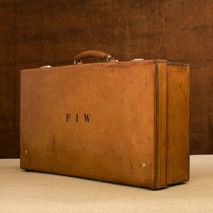 View at a diagonal angle of the lid side of the leather case, circa 1925, handle at the top, just showing nickel plated brass locks at the top and the initials  F.I.W. Brown and cream background.
