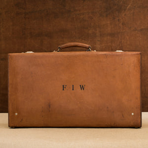 View of the lid side of the leather case, circa 1925, handle at the top, just showing nickel plated brass locks at the top and the initials F.I.W.  Brown and cream background.