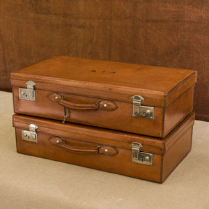 Front view of a matching pair of English leather cases, circa 1925, one on top of the other at a slight angle. The top suitcase has the initials F.I.W. Both have nickel plated brass locks. Brown and cream background.