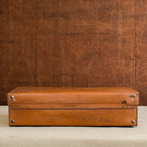 Rear view, showing the stitching of the hinge of the English leather case, circa 1925. Brown and cream background.