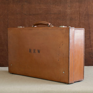 View at a diagonal angle of the lid side of the leather case, circa 1925, handle at the top, just showing nickel plated brass locks at the top and the initials R.E.W. Brown and cream background.