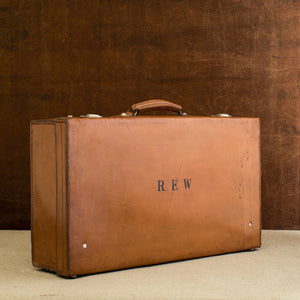 Front view of the lid side of the leather case, circa 1925, handle at the top, just showing nickel plated brass locks at the top and the initials R.E.W. Brown and cream background.