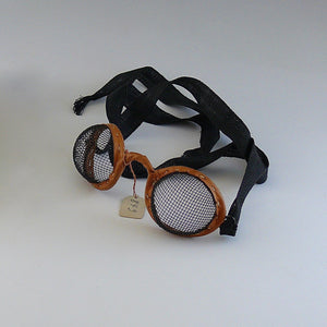 Close up of vintage motoring or aviation goggles with fine mesh eye covers and fabric strap by Kraus & Co, 1900-1950. White background.