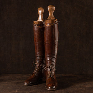 Front view of a pair of brown leather polo boots including their wooden trees made for Earl Spencer, Althorp Estate. They are laced up and at a three quarter position on a brown background.