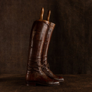 Side view of a pair of brown leather polo boots including their wooden trees made for Earl Spencer, Althorp Estate. They are laced up and placed sideways, rear boot slightly in front on a brown background.