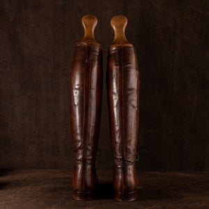 Rear view of a pair of brown leather polo boots including their wooden trees, made for Earl Spencer, Althorp Estate. Rear of boots showing, placed side by side on a brown background.