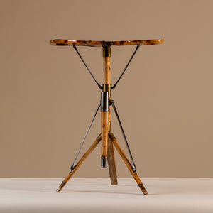 The image shows an Edwardian shooting stick seat forming a three legged stool in beech wood, brass and steel, circa 1910. The stool sits central on a beige and cream background with tripod legs splayed and the seat opened facing forwards.