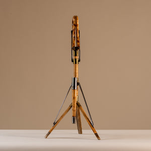 The image shows an Edwardian shooting stick with the tripod base open and the seat at the top closed together. Made of beech wood, brass and steel, circa 1910. The stool sits central on a beige and cream background with tripod legs splayed and the seat closed facing forwards.