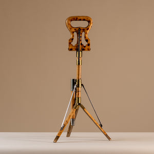 The image shows an Edwardian shooting stick with the tripod base open and the seat at the top closed together. Made of beech wood, brass and steel, circa 1910. The stool sits central on a beige and cream background with tripod legs splayed and the seat closed facing sideways.