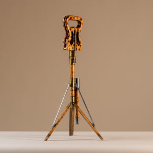 The image shows an Edwardian shooting stick with the tripod base open and the seat at the top closed together. Made of beech wood, brass and steel, circa 1910. The stool sits central on a beige and cream background with tripod legs splayed and the seat closed facing a diagonal angle.