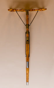 The image is from above, it shows an Edwardian shooting stick with the tripod base in the steel and beech wood cover turning it into a shooting stick seat. The seat at the top is opened into a seat. All made of beech wood, brass and steel, circa 1910. They are against a beige and cream background.