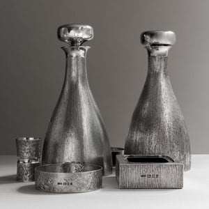Front view of two silver 'bark finish' decanter with polished silver stoppers side by side, with hallmarks, London 1970's with makers mark HOL - House of Lawrian, with silver ashtray to front right, silver coaster front left, silver spirit measure left side. Against a grey background.