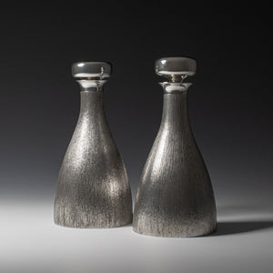 Front view of two silver 'bark finish' decanter with polished silver stoppers side by side, with hallmarks, London 1970's with makers mark HOL - House of Lawrian, against a grey background.