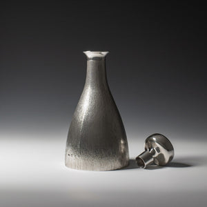 Front view of silver 'bark finish' decanter with polished silver stopper to the right of the picture with hallmark, London 1973 with makers mark HOL - House of Lawrian, against a grey background.