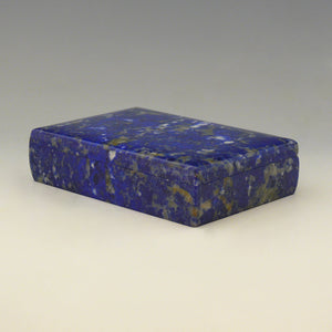 A front view from an angle with the front right corner in the foreground of a Lapis Lazuli box with a cobalt blue base colour and white, beige and dark blue mottling running through the stone. white background.