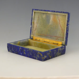 A front view at an angle of an open stone box with a yellow stone inside and gilt hinge along the edge adjoining the lid. The outside of the box is Lapis Lazuli with a cobalt blue base colour and white, beige and dark blue mottling running through the stone. white background.