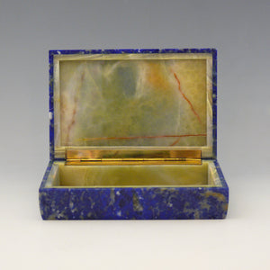 A front view of an open stone box with a yellow stone inside and gilt hinge along the edge adjoining the lid. The outside of the box is Lapis Lazuli with a cobalt blue base colour and white, beige and dark blue mottling running through the stone. white background.